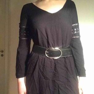En fin svart klänning som man kan ha ett snyggt skärp till dock är inte skärpet på bilden till salu och på baksidan är det öppet och det är snören som man kan göra vilken snöring man känner för.