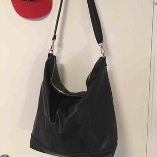 Fin och praktisk väska med axelband, rymlig, helt svart med silver detaljer. Helt oanvänd, precis som ny. Skriv gärna för frågor. Nypris 300kr. Frakt tillkommer.
