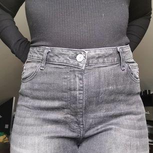 Superfina gråa jeans med hål på knät! Går till fotknölen på mig som är 162cm. Avklippt design nedtill. Midjan är 86cm. 🌼