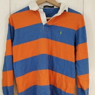 Orange/blå polo från Ralph Lauren, påminde mig om Tyler the creator när den köptes, men användes tyvärr aldrig. Ganska liten i storleken, passar small/medium.