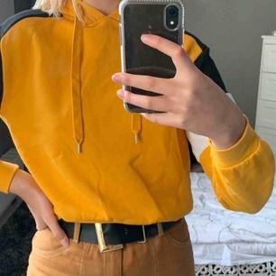 En gul mellanlång hoodie med vitt och svart på armarna. Frakt tillkommer