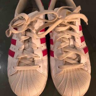Fina Adidas Superstar sneakers med rosa detaljer.