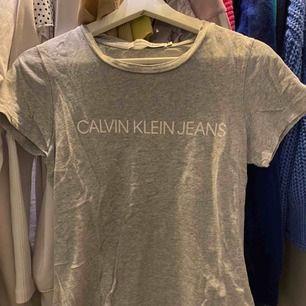 Calvin Klein tshirt. Rätt så använd men i super bra skick. Texten har inte lossnat eller liknande. Frakt tillkommer på 55kr.