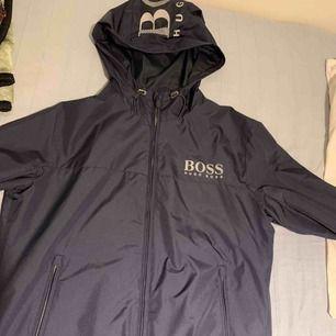 Helt oanvänd Hugo boss vår/höst jacka. kan användas under regn också. Pris kan diskuteras, det är bara att buda på :)