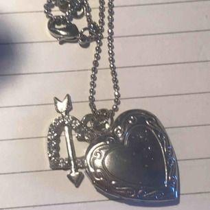 Silvrigt halsband/ acesoar i form av ett hjärta som håt att öppna och stoppa in 2 små bilder på halsbandet sitter ett mindre hjärta brevid i glittriga stenar kedjan är kulformad. Vet inte märket då det är köppt i los angeles (usa) för 200kr