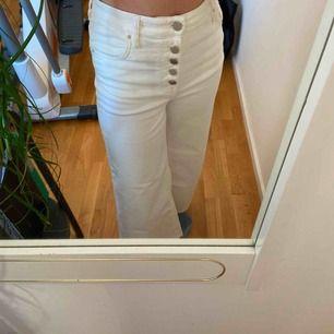 Vita flarade byxor med knappar i fram från Urban outfitters. Frakt tillkommer eller möts.