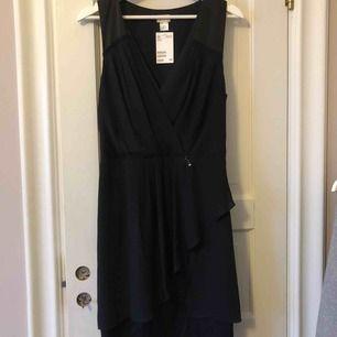 Helt oanvänd kortare svart klänning med volanger. Lappen kvar. Köpt för 499kr❤️