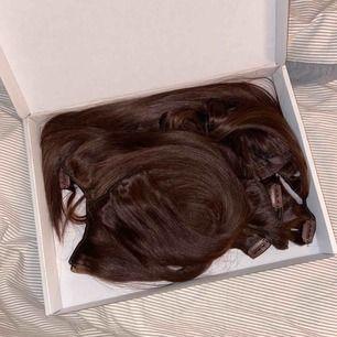 Helt nya set från Rapunzel of Sweden: clip on set 7 pieces och ponytail. I färgen 2.3 (chokladbrun). Ej kommit till användning och därav väldigt bra skick. Säljer båda delarna tillsammans för 1000kr!!!! Ord pris: 1700kr. Köpare står för frakt.