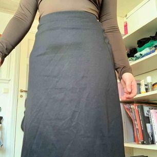 Kjol i midilängd i bomull. Ganska tjockt material. Strechig. Slutar under knäna på mig som är ca 160 cm. Fri frakt!