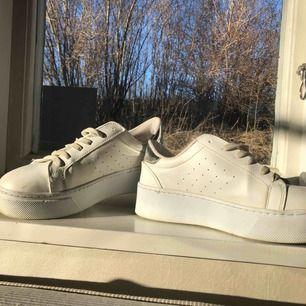 Vita skor med silver på hälen. Hög sula storlek 37. Köparen betalar frakten.