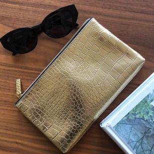 Snygg guldig necessär i ormskinn från Estee Lauder. Men använder mer som handväska för ett finare tillfälle. Rymmer telefonen, kort, lite smink m.m.