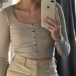 Beige croppad långärmad tröja med knappar framtill. Ribbad och väldigt skön och fin! Aldrig använd! Finns även en vit i storlek M om nån är intresserad.