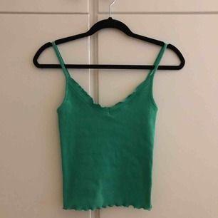 Säljer en jättegullig grön linne, perfekt till sommaren! som är ribbad och har små volanger på kanterna, från Gina tricot⚡️🪐