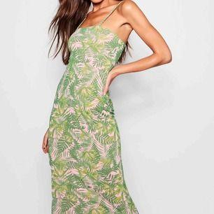Maxiklänning i gröna nyanser med inslag av rosa. Jag är 168 cm lång och klänningen når hela vägen ner.