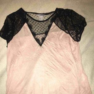 Mjuk, ljusrosa tröja från hm som har ett svart spetsmönster vid armarna, brösten och ryggen