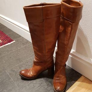 Stövlarna har höga skaft och remmar vid foten. Skinnet har snygg patina och de är sköna att gå i eftersom klacken är bred. De kan hämtas på Södermalm eller på annan plats i Stockholm. Annars betalar du frakten