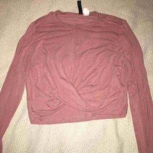 Rosa, långärmad, croppad tröja från hm med en design på framsidan som gör så att materialet korsar. Priset kan diskuteras :)
