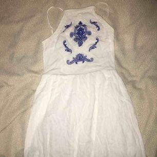 Vit klänning med blå mönster vid brösten. Är lagrad där nere (som visas i tredje bilden). Priset kan diskuteras :)