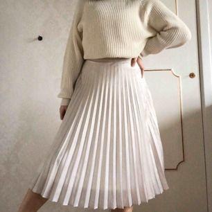 SÅLD!!! Underbar veckad kjol i beige eller krämvit  (som glänser) ! Sjukt söt till sommaren eller på fest! Några trådar har tyvärr gått, så skicket är inte nytt. Skickar bild på det om du vill :)