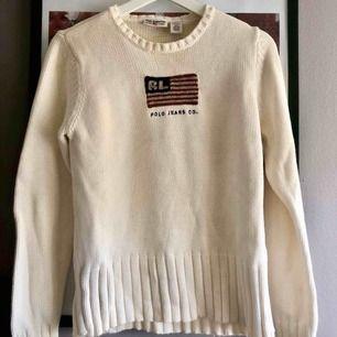 Vintage tröja från Polo Jeans Ralph Lauren. Beige/vit stickad tröja med amerikanska flaggan, samt polos klassiska signatur RL inbroderat. Perfekt till hösten/vinterns mys.  Strl M
