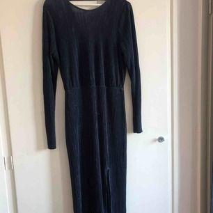 Marinblå plisserad långklänning med öppen rygg från Gina tricot. Storlek L Möts helst upp i Centrala Stockholm