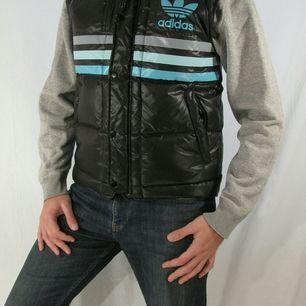 Svart Adidas dunväst i glansigt material. Bra skick! Personen på bilderna är 183 cm.