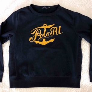 Marinblå sweatshirt med gult påsytt tryck från Polo Ralph Lauren  Köpt i USA för 2 år sen men använd max 2 gånger sedan dess