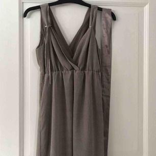 Vitprickig moccafärgad Sommar/studentklänning Använd vid ett tillfälle.  Sidenband medföljer för att knyta runt magen.