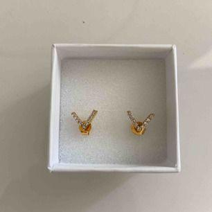 """Guldiga örhängen med små """"diamanter"""" i formen av ett V från syster P. Super fint skick:)"""