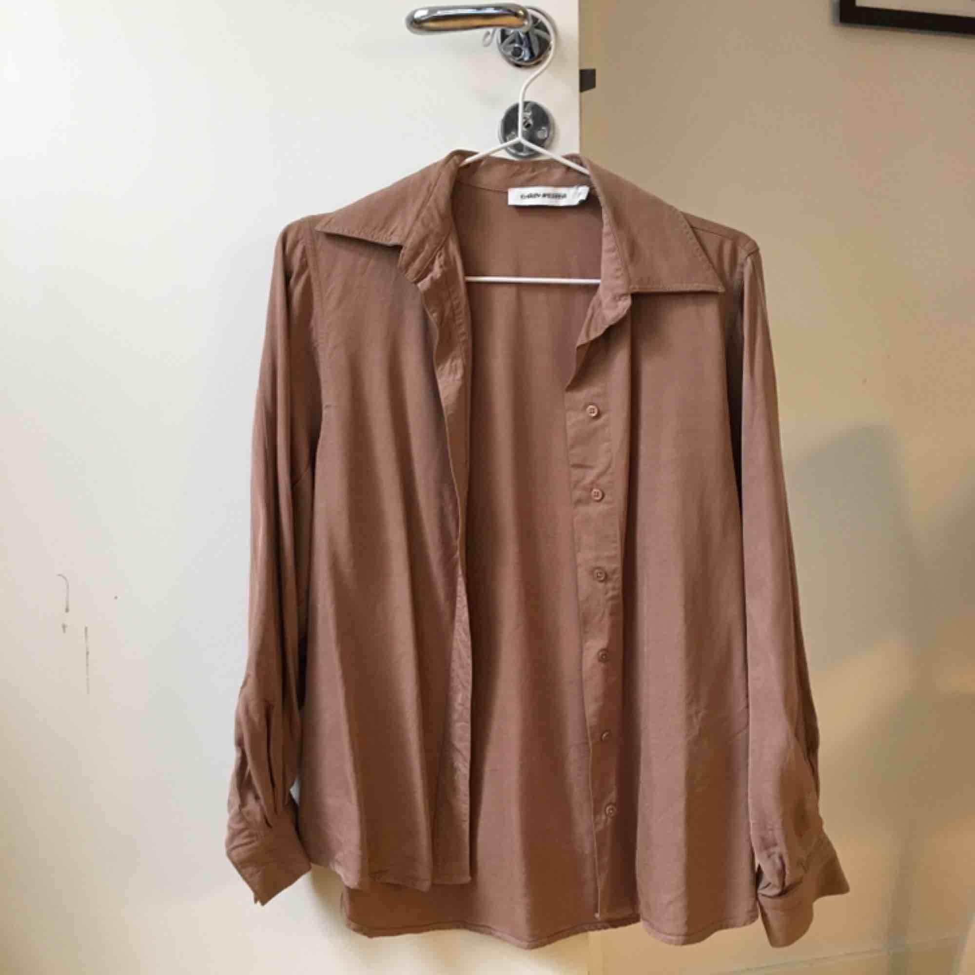 Nyköpt skjorta från Carin Wester i skönt material. Säljes p.g.a. tvättade i för hög temperatur så krympte lite en storlek från 36 till 34. Därmed tyvärr lite försliten för mig. Priset är exkl frakt 🌱. Skjortor.