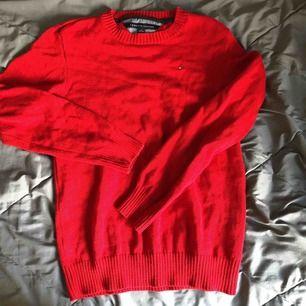 Som ny, röd stickad Tommy Hilfiger tröja. Stl ungdom 16/18 är som stl XS Köparen står för porto