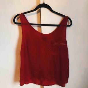 Rött linne i silkesmaterial med guldig dragkedja vid bröstet