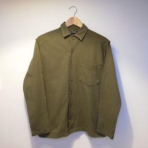 Khakigrön vintage skjorta från H&M i stl S herr. Sitter snyggt oversize på mig som har stl XS dam, skulle säga att den passar dam upp till stl M. Gjord i pikétröja-material. Frakt 55 kr.