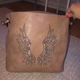 Väska med stenar som vingar, var jätte populär! Rymlig men fortfarande en handväska, ALDRIG använd så är i nyskick, inga defekter