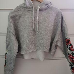 Grå croppad hoodie med broderier. I storlek L passar även XS och S om man vill ha den mer oversize. Skriv för fler bilder/frågor