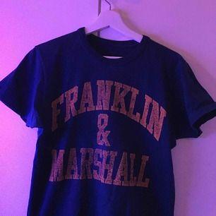 Franklin & Marshall t-shirt i mörkblå/marinblå färg. Hyfsat använd och därmed priset. Men förövrigt skön och soft t-shirt.