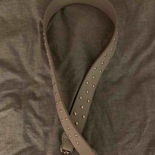 Ett super snyggt trendigt bagstrap i grått med silver nitar, (typ oanvänd) .  Bandet är 95cm långt!