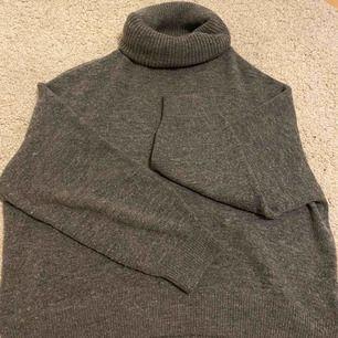 Grå stickad tröja från hm, fint skick använd ett fåtal gånger. Lång hals som går att styla hur man vill! Köparen står för frakten.