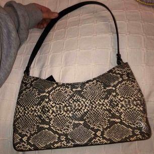 En väldigt fin väska med orm skinn (inte äkta). Köpt utomlands. Väldigt bra skick, enbart använt några få gånger. Köpt för 400kr.