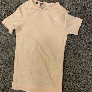 Jättefin Gymshark t-shirt i storlek S. (Färgen är mer rosa irl) Aldrig använt då den var för liten. Nypris 400kr. Kan frakta men köparen står för frakten. Kontakta för fler bilder eller frågor. 💛