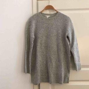 Stickad tröja i längre modell med slits på sidorna. Från H&M. Använd men i bra skick