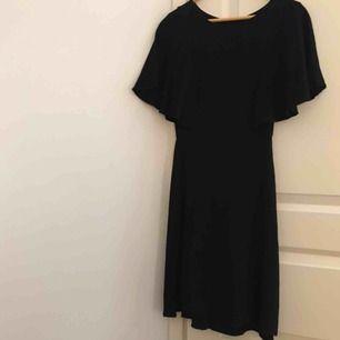 Svart klänning med fladdriga ärmar och avtagen midja. Går ungefär till knäna på mig som är 162cm. Säljs då den inte används längre. Är i nyskick!