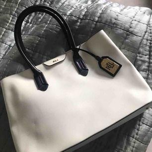 Vit läderväska från ralph lauren med marinblå detaljer. Självklart äkta. Använd endast två gånger. Som ny. Nypris ca 2500.