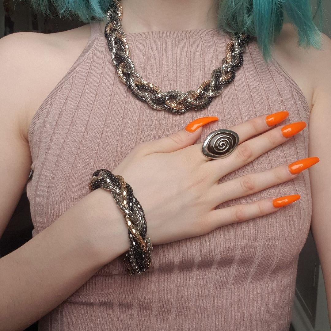 Jättefint flätat halsband och armband i guld, silver och svart. Säljer billigt då dem är i bra skick förutom att knäppet på halsbandet gått sönder (se bild 3) men går fortfarande att knäppa såklart :) . Accessoarer.
