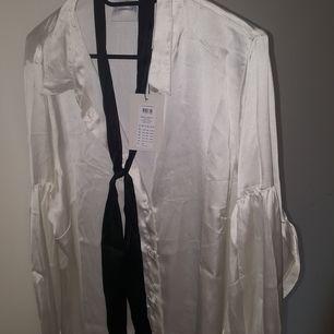 Juna Rose blus med svart band som en slips el bara hänga löst . Storlek 48 helt ny ej ens provad.  Jätte fin kvalité.