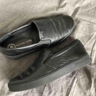 """Snygga helsvarta sneakers från Michael Kors! Använda fåtal gånger! Äkta läder så tåliga skor! Kommer smörja in dem med läderolja osv, så """"rynkorna"""" framme på skon kommer inte vara lika synliga. Dock syns dom inte alls när man har skorna på sig!"""