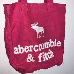 Rosa väska från Abercrombie and Fitch. Perfekt att ha med till stranden eller liknande. Måttligt använd. Finns dragkedja att stänga med samt mindre fack inuti väskan. Köparen står för frakt, fler bilder kan skickas.