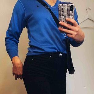 Blå tröja med en häst på vänster bröst. Skönt material och v-ringad.Fler bilder kan skickas, köparen betalar frakt.