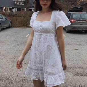 Gullig vit vintage klänning (lite kort på mig 172cm). Volanger i slutet av kjolen och knytband i ryggen!