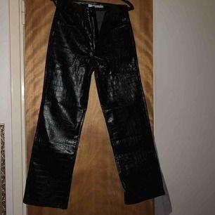 """Ett par faux läder byxor med """"krokodil"""" mönster. Raka och lössittande i modellen och möjligtvis lite kortare i längden. Jag köpte dem här byxorna förra hösten har aldrig använt dem så dem är i bra skick"""